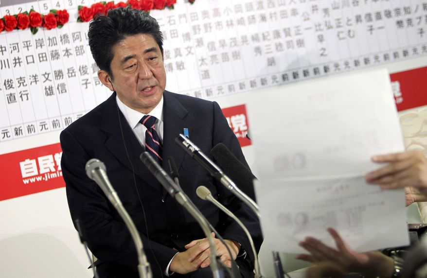 Shinzo Abe, leader of the main Japanese opposition Liberal Democratic Party, answers a reporter's question at party headquarters in Tokyo on Sunday night, Dec. 16, 2012. The conservative LDP stormed back into power in parliamentary elections Sunday after three years in opposition, exit polls showed, signaling a rightward shift in the government that could further heighten tensions with rival China. (AP Photo/Junji Kurokawa)