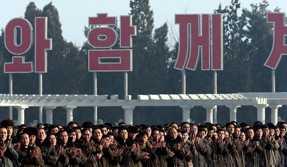 """North Koreans clap as they stand beneath part of a huge slogan that translates as """"The great leaders Comrade Kim Il-sung and Comrade Kim Jong-il will always be with us"""" at a reopening ceremony at the Kumsusan Palace of the Sun in Pyongyang, North Korea, on Monday, Dec. 17, 2012. North Korean officials reopened the mausoleum to mark the first anniversary of the death of Kim Jong-il. (AP Photo/Ng Han Guan)"""