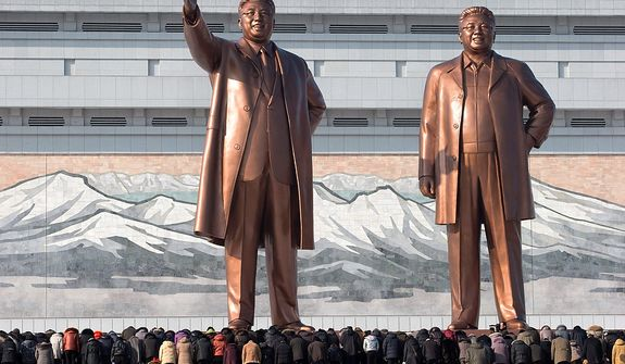 North Koreans bow before the statues of late leaders Kim Il-sung (left) and Kim Jong-il at Mansu Hill in Pyongyang, North Korea, on Monday, Dec. 17, 2012. Sirens wailed for three minutes at noon Monday in honor of the first anniversary of the death of Kim Jong-il. (AP Photo/Ng Han Guan)