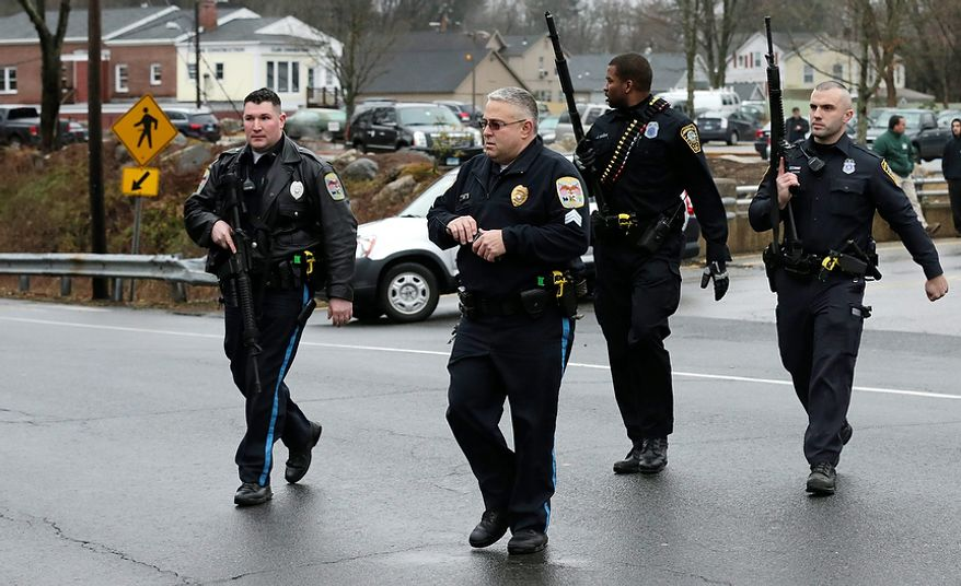Police officers cross the road after searching a strip mall near an elementary school that was in a lockdown in Ridgefield, Conn., on Monday, Dec. 17, 2012, after a suspicious person was seen near a train station close by. On Friday, authorities say, a gunman killed his mother at their home and then opened fire inside the Sandy Hook Elementary School in Newtown, Conn., killing 26 people, including 20 children, before taking his own life. (AP Photo/Charles Krupa)