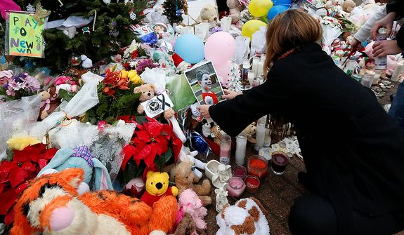 A woman puts a photo of a child on a makeshift memorial in the Sandy Hook village of Newtown, Conn., on Monday, Dec. 17, 2012, as the town mourns victims of the school shooting. (AP Photo/Julio Cortez)