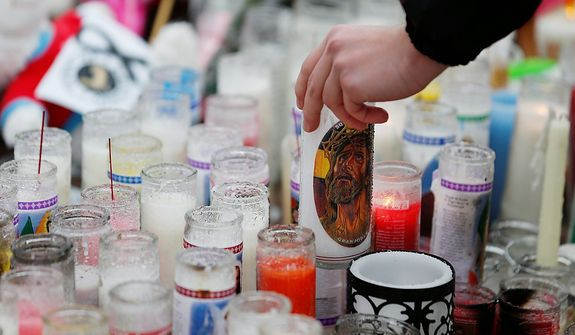Ryan Bartolotta, 17, picks up a candle to drain out rainwater and light it on a makeshift memorial in the Sandy Hook village of Newtown, Conn., on Monday, Dec. 17, 2012, as the town mourns victims of the school shooting. (AP Photo/Julio Cortez)