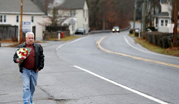 A man walks with flowers in the Sandy Hook village of Newtown, Conn., on Monday, Dec. 17, 2012, as the town mourns those killed in Friday's school shooting. (AP Photo/Julio Cortez)