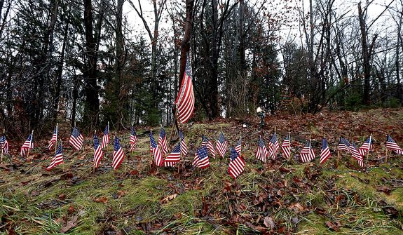 Twenty-seven small U.S. flags adorn a large flag on a makeshift memorial on the side of Highway 84 near the Newtown, Conn., town line on Monday, Dec. 17, 2012, as residents mourn those killed by gunman Adam Lanza. (AP Photo/Julio Cortez)