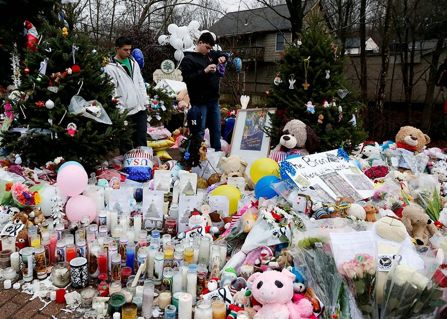Ryan Bartolotta (right), 17, and Ray Massi, 18, relight candles that were put out by rain at a makeshift memorial in the Sandy Hook village of Newtown, Conn., on Monday, Dec. 17, 2012, as the town mourns the victims of Friday's school shooting. (AP Photo/Julio Cortez)