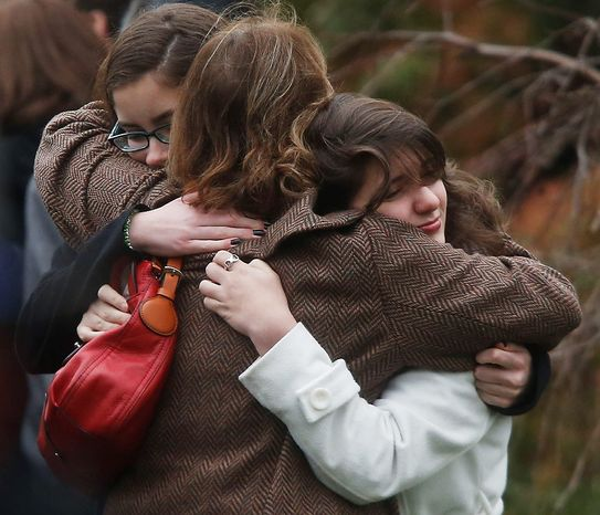 Mourners hug each other before a funeral service for 6-year-old Noah Pozner, Monday, Dec. 17, 2012, in Fairfield, Conn. Pozner was killed when a gunman walked into Sandy Hook Elementary School in Newtown, Conn., Friday and opened fire, killing 26 people, including 20 children. (AP Photo/Jason DeCrow)