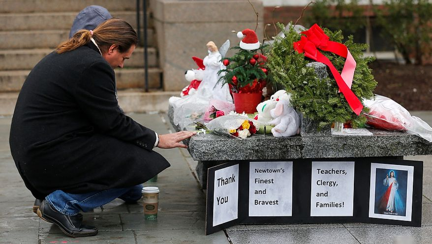 A couple pause at a memorial outside town hall in Newtown, Conn., Monday, Dec. 17, 2012. A gunman opened fire at Sandy Hook Elementary School in the town, killing 26 people, including 20 children before killing himself on Friday. (AP Photo/Charles Krupa)
