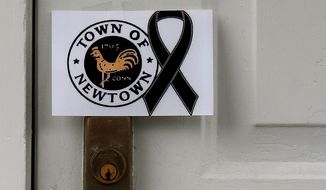 ** FILE ** A sign showing the town seal and a black ribbon is posted on the door of an antique colonial home in the historic district near the funeral for 6-year-old student and shooting victim Jack Pinto in Newtown, Conn., Monday, Dec. 17, 2012. A gunman opened fire at Sandy Hook Elementary School in the town, killing 26 people, including 20 children before killing himself on Friday. (AP Photo/Charles Krupa)
