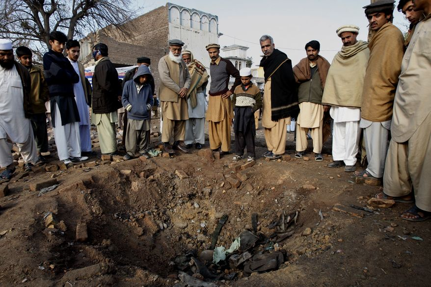 Residents examine a crater caused by Saturday night's car bombing by Taliban militants close to the international airport in Peshawar, Pakistan, on Sunday, Dec. 16, 2012. (AP Photo/Mohammad Sajjad)