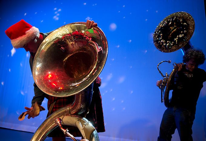 """Gunnar Tokar (left), 15, of Damascus, Md., polishes his tuba while Anthony Makusky, 17, of Frederick, Md., makes his way onto the stage before the start of the rehearsal for """"Tuba Christmas 2012"""" at the Millennium Stage at the Kennedy Center in Washington on Thursday, Dec. 13, 2012. The two musicians were among hundreds of tuba players who came to the Kennedy Center to play in the concert, which originated in 1974 as a tribute to the late artist-teacher William J. Bell, who was born on Christmas Day in 1902. Participants were asked to wear bright colors. They rehearsed for two hours before performing onstage at 6 p.m. (Barbara L. Salisbury/The Washington Times)"""