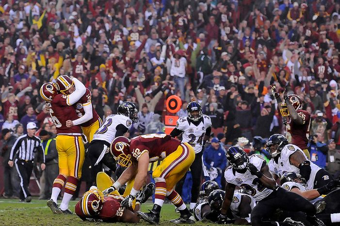 Washington Redskins kicker Kai Forbath (2) leaps into the arms of holder Sav Rocca (6) after kicking a 34-yard field goal to beat the Baltimore Ravens 31-28 in overtime at FedEx Field in Landover, Md., on Sunday, Dec. 9, 2012. (Preston Keres/Special to The Washington Times)