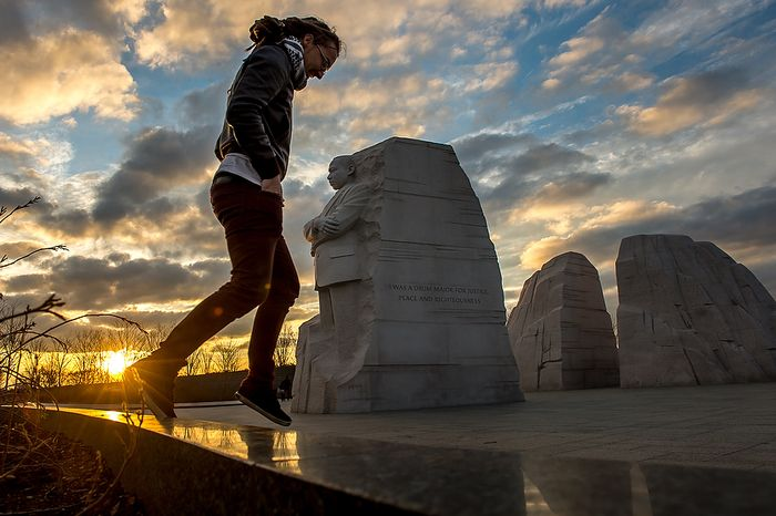 """Jarrod McKenna of Perth, Australia, jumps down from a wall after taking a photograph of the Martin Luther King Jr. National Memorial on Tuesday, Dec. 11, 2012, the same day the Department of the Interior announced it will remove a controversial """"drum major"""" quote on the side of the memorial (pictured center) in Washington. The quote, which paraphrases King's words, was originally marked to be replaced by the full quote. (Andrew Harnik/The Washington Times)"""
