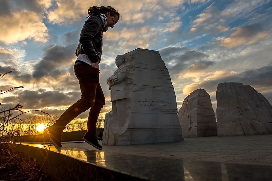 "Jarrod McKenna of Perth, Australia, jumps down from a wall after taking a photograph of the Martin Luther King Jr. National Memorial on Tuesday, Dec. 11, 2012, the same day the Department of the Interior announced it will remove a controversial ""drum major"" quote on the side of the memorial (pictured center) in Washington. The quote, which paraphrases King's words, was originally marked to be replaced by the full quote. (Andrew Harnik/The Washington Times)"