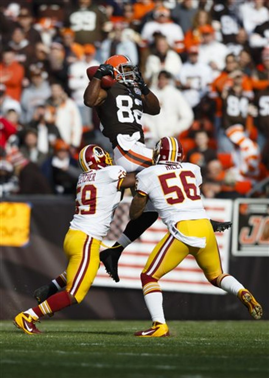 Cleveland Browns tight end Benjamin Watson (82) makes a reception as Washington Redskins inside linebacker London Fletcher (59) and inside linebacker Perry Riley (56) defend in the first half of an NFL football game in Cleveland, Sunday, Dec. 16, 2012. (AP Photo/Rick Osentoski)
