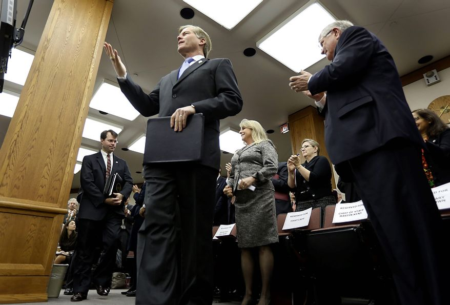 Virginia Gov. Bob McDonnell acknowledges the applause as as he arrives to address a joint meeting of the House Appropriations and Senate Finance committees at the Capitol Monday, Dec. 17, 2012 in Richmond, Va.  McDonnell delivered his 2013 budget before the committees.  (AP Photo/Steve Helber)