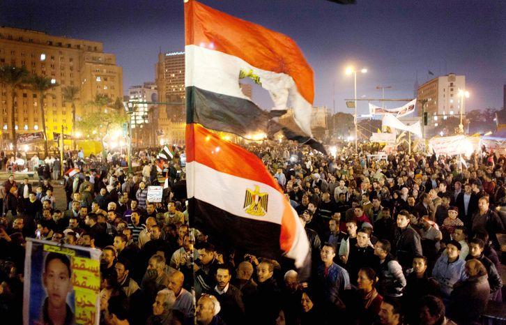 Egyptians opposing President Mohammed Morsi carry flags in Tahrir Square, Cairo, on Tuesday. (Associated Press)