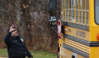 Easton police officer J. Sollazzo waves to returning children as their bus pulls into Hawley School, Tuesday, Dec. 18, 2012, in Newtown, Conn. Classes resume Tuesday for Newtown schools except those at Sandy Hook. (AP Photo/Jason DeCrow)