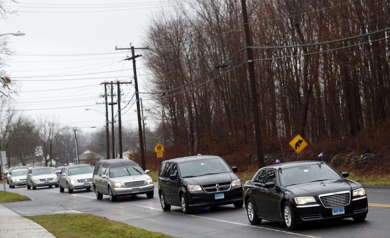 A funeral procession makes its way toward St. Rose of Lima Roman Catholic Church in Newtown, Conn., for services for 6-year-old James Mattioli on Tuesday, Dec. 18, 2012. (AP Photo/Julio Cortez)