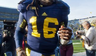 Michigan quarterback Denard Robinson (16) makes his way off the Michigan Stadium field after an NCAA college football game against Iowa, Saturday, Nov. 17, 2012, in Ann Arbor, Mich. Michigan won 42-17. (AP Photo/Tony Ding)