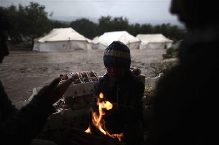 Syrians, who fled their homes with their families, gather around a fire to warm themselves at a makeshift vegetables store in a camp for the displaced in the village of Atmeh, Syria, Tuesday, Dec. 18, 2012. (AP Photo/Muhammed Muheisen)