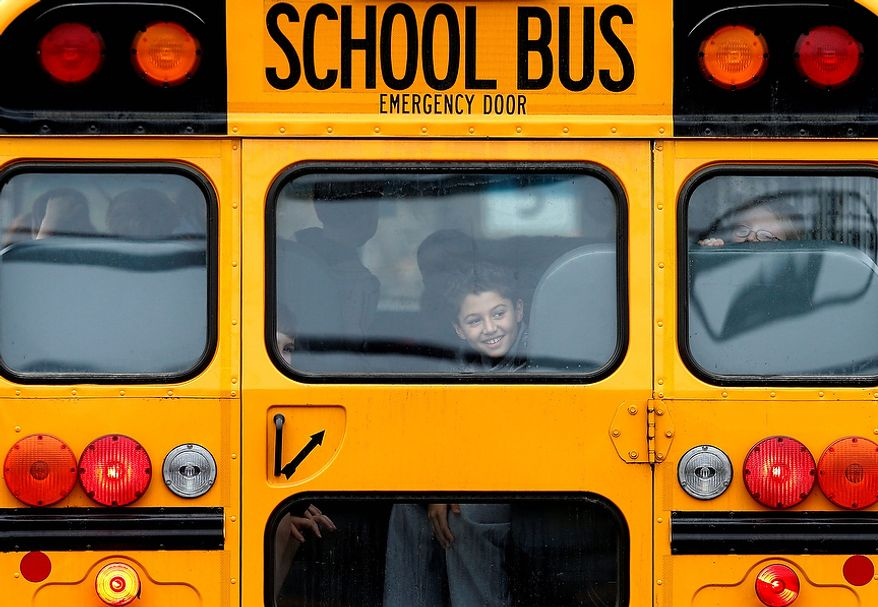 A returning student smiles as his bus school bus pulls into Hawley School, Tuesday, Dec. 18, 2012, in Newtown, Conn.  Classes resume Tuesday for Newtown schools except those at Sandy Hook. Buses ferrying students to schools were festooned with large green and white ribbons on the front grills, the colors of Sandy Hook. At Newtown High School, students in sweatshirts and jackets, many wearing headphones, betrayed mixed emotions.  Adam Lanza walked into Sandy Hook Elementary School in Newtown,  Friday and opened fire, killing 26 people, including 20 children, before killing himself.(AP Photo/Jason DeCrow)
