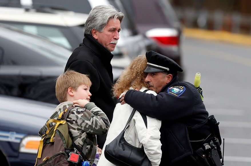 Easton police officer J. Sollazzo embraces a couple walking a young student into Hawley School, Tuesday, Dec. 18, 2012, in Newtown, Conn.  Classes resume Tuesday for Newtown schools except those at Sandy Hook. Buses ferrying students to schools were festooned with large green and white ribbons on the front grills, the colors of Sandy Hook. At Newtown High School, students in sweatshirts and jackets, many wearing headphones, betrayed mixed emotions.  Adam Lanza walked into Sandy Hook Elementary School in Newtown,  Friday and opened fire, killing 26 people, including 20 children, before killing himself.(AP Photo/Jason DeCrow)