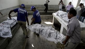 Rescue workers at a hospital morgue in Karachi, Pakistan, carry the body of a female polio worker killed by unknown gunmen on Tuesday, Dec. 18, 2012. (AP Photo/Fareed Khan)