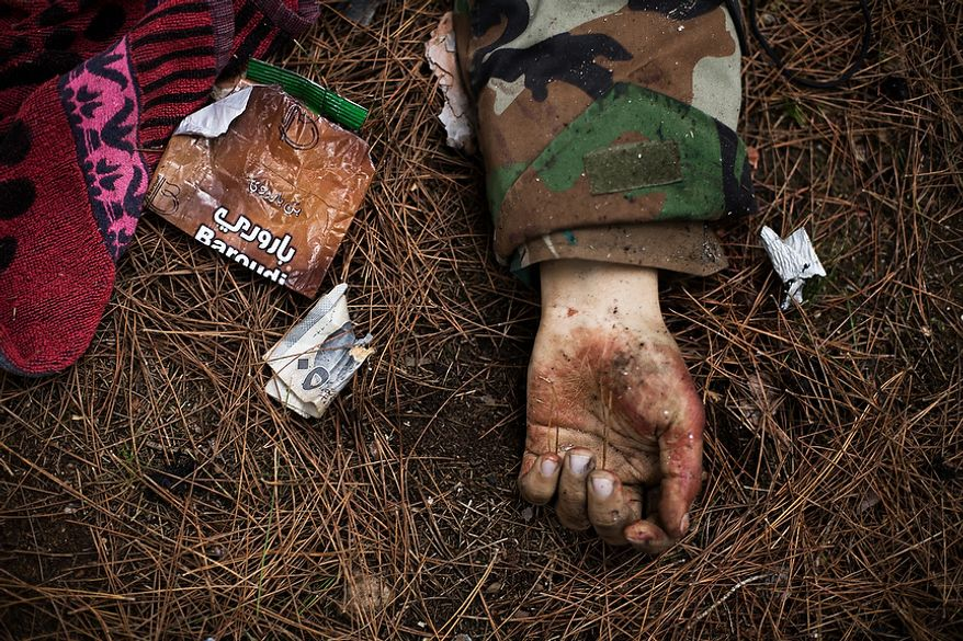 The body of a Syrian Army soldier lies on the ground after heavy clashes with government forces at a military academy besieged by the rebels in Tal Sheer, Syria, Sunday, Dec 16, 2012. (AP Photo / Manu Brabo)