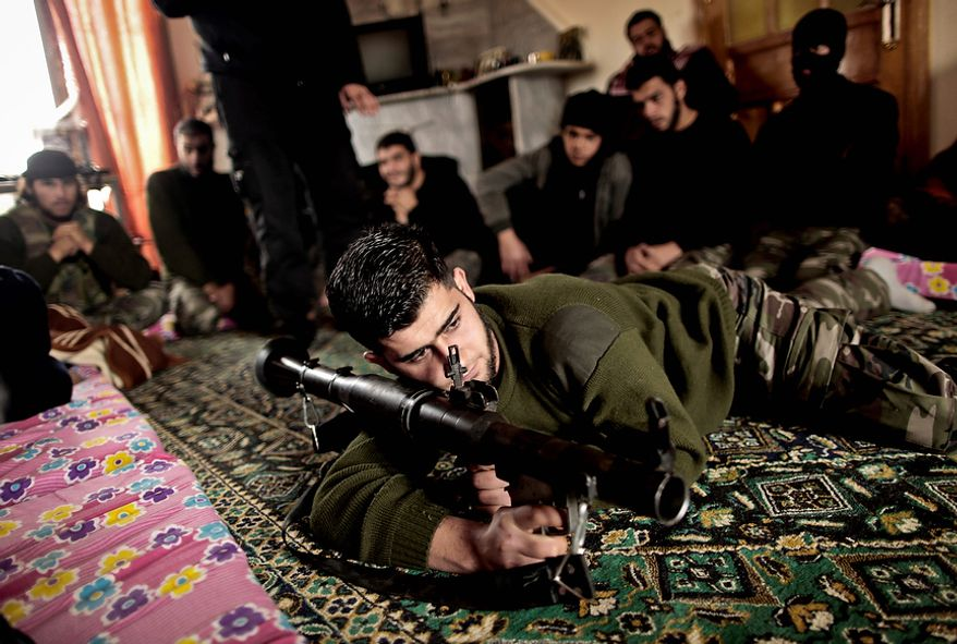 In this Monday, Dec. 17, 2012 photo, Syrian rebels listen to their trainer while teaching them how to use the RPG during a training session in Maaret Ikhwan, near Idlib, Syria. The training is part of an attempt to transform the rag-tag rebel groups into a disciplined fighting force. (AP Photo/Muhammed Muheisen)