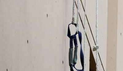 A harness and the end of a rope dangles Tuesday from a window of the Metropolitan Correctional Center in Chicago. Two convicted bank robbers used a knotted rope made from bedsheets to escape from their lockup cell, which was 20 stories above the ground. They were still at large Wednesday night. (Associated Press)