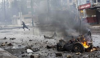 A boy runs for cover after a mortar shell hit a street and killed several people in the Bustan Al-Qasr district of Aleppo, Syria, on Monday, Dec. 17, 2012. (AP Photo/Narciso Contreras)