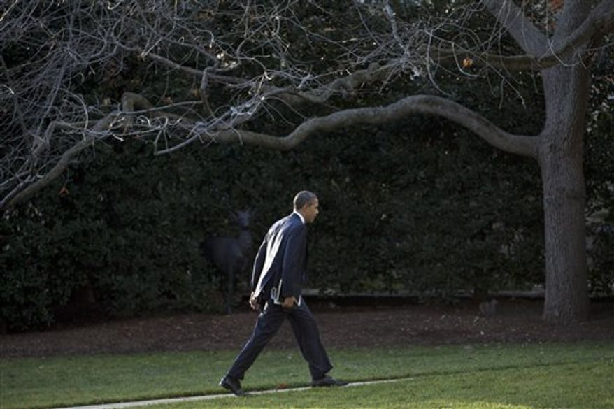 President Barack Obama walks to the Oval Office of the White House as he returns from greeting members of the staff, Tuesday, Dec. 18, 2012, in Washington. (AP Photo/Carolyn Kaster)