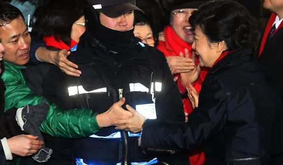 South Korean presidential candidate Park Geun-hye of the ruling Saenuri Party shakes hands with a supporter as she leaves her home to head to her office in Seoul on Wednesday, Dec. 19, 2012. (AP Photo/Yonhap)