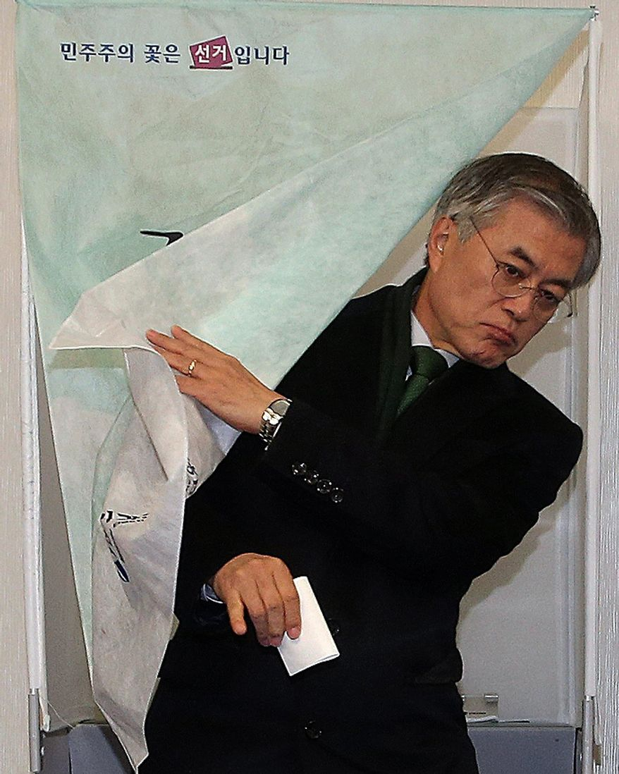 Moon Jae-in, South Korean opposition Democratic United Party presidential candidate, leaves a voting booth to cast his ballot in South Korea's presidential election at a polling station in Busan, South Korea, on Wednesday, Dec. 19, 2012. (AP Photo/ Yonhap, Kim Hyun-tai)