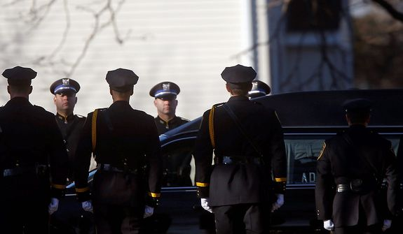 A hearse bearing the body of Victoria Soto drives past a police honor guard as it arrives for her funeral service at Lordship Community Church, Wednesday, Dec. 19, 2012, in Stratford, Conn.  Soto was killed when a gunman forced his way into Sandy Hook Elementary School in Newtown Dec. 14,  and opened fire, killing 26 people, including 20 children. (AP Photo/Jason DeCrow)