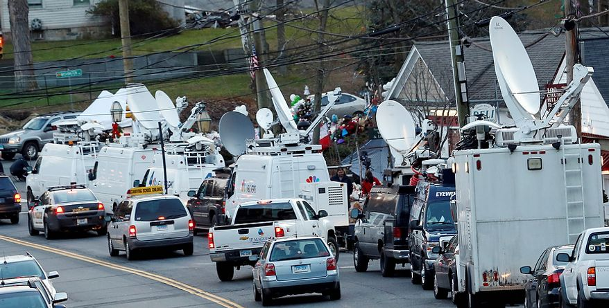 """A van with a sign reading """"carrying school children"""", center left, drives behind a police vehicle through a main road in the Sandy Hook village of Newtown, Conn., as the strong media presence is felt in the aftermath of the elementary school shooting that shocked the small, quiet town, Wednesday, Dec. 19, 2012. News about the shooting spread quickly across the world, prompting media outlets to set camp in the small town. The gunman, Adam Lanza, walked into Sandy Hook Elementary School in Newtown, Conn., Dec. 14, and opened fire, killing 26 people, including 20 children, before killing himself. (AP Photo/Julio Cortez)"""