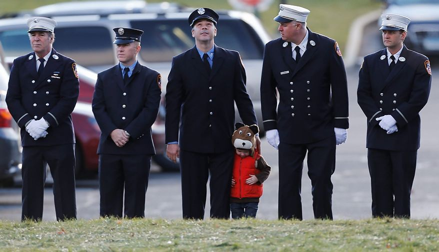 A child lines up with firefighters outside the funeral for school shooting victim Daniel Gerard Barden,at St. Rose of Lima Catholic Church in Newtown, Conn., Wednesday, Dec. 19, 2012.  According to firefighters, Daniel wanted to be a firefighter when he grew up and they honored him at the service. Gunman Adam Lanza opened fire killing 26 people, including 20 children, at Sandy Hook Elementary School in Newtown before killing himself on Friday. (AP Photo/Charles Krupa)