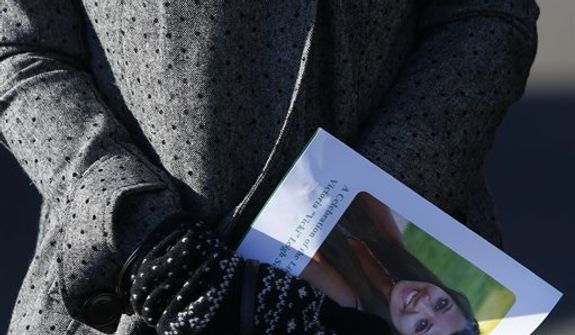 A mourner carries a program as she leaves the funeral service of Victoria Soto at Lordship Community Church, Wednesday, Dec. 19, 2012, in Stratford, Conn.  Soto was killed when Adam Lanza walked into Sandy Hook Elementary School in Newtown, Conn., Dec. 14, and opened fire, killing 26 people, including 20 children, before killing himself. (AP Photo/Jason DeCrow)