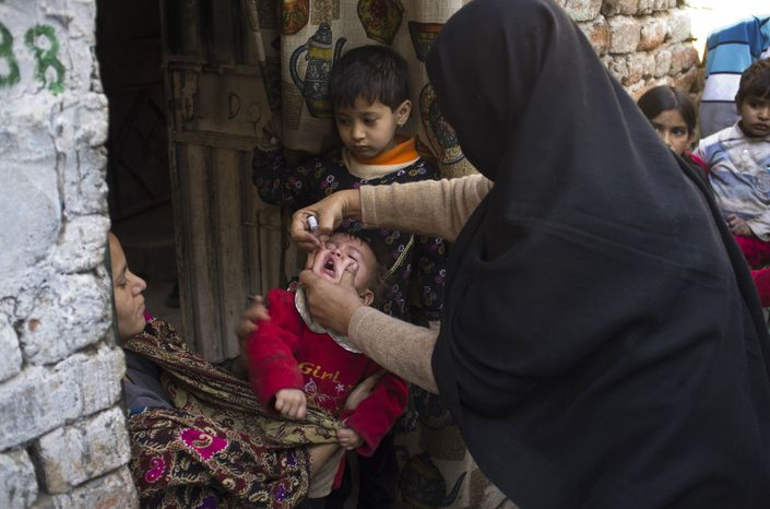 A Pakistani polio worker administers the oral polio vaccine to an infant in a Christian colony in the slums of Islamabad on Wednesday, Dec. 19, 2012. (AP Photo/B.K. Bangash)
