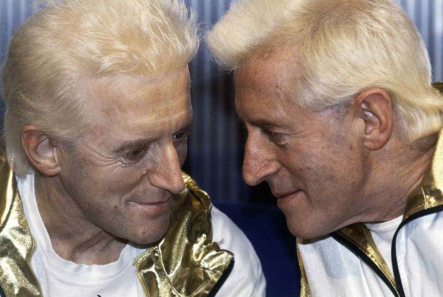 ** FILE ** In this Dec. 17, 1986, file photo, Jimmy Savile, right, poses for photographers with a wax work model at Madame Tussauds museum in London. (AP Photo/John Redman, File)