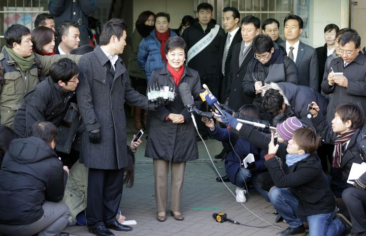 South Korean presidential candidate Park Geun-hye (center) of the ruling Saenuri Party speaks to the media after casting her ballot in the presidential election at a polling station in Seoul on Wednesday, Dec. 19, 2012. (AP Photo/Lee Jin-man)