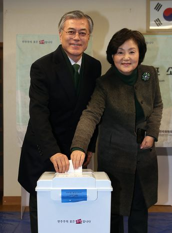Moon Jae-in, the South Korean opposition Democratic United Party's presidential candidate, and his wife, Kim Jung-sook, cast their votes in the presidential election at a polling station in Busan, South Korea, south of Seoul, on Wednesday, Dec. 19, 2012. (AP Photo/Yonhap, Kim Hyun-tai)