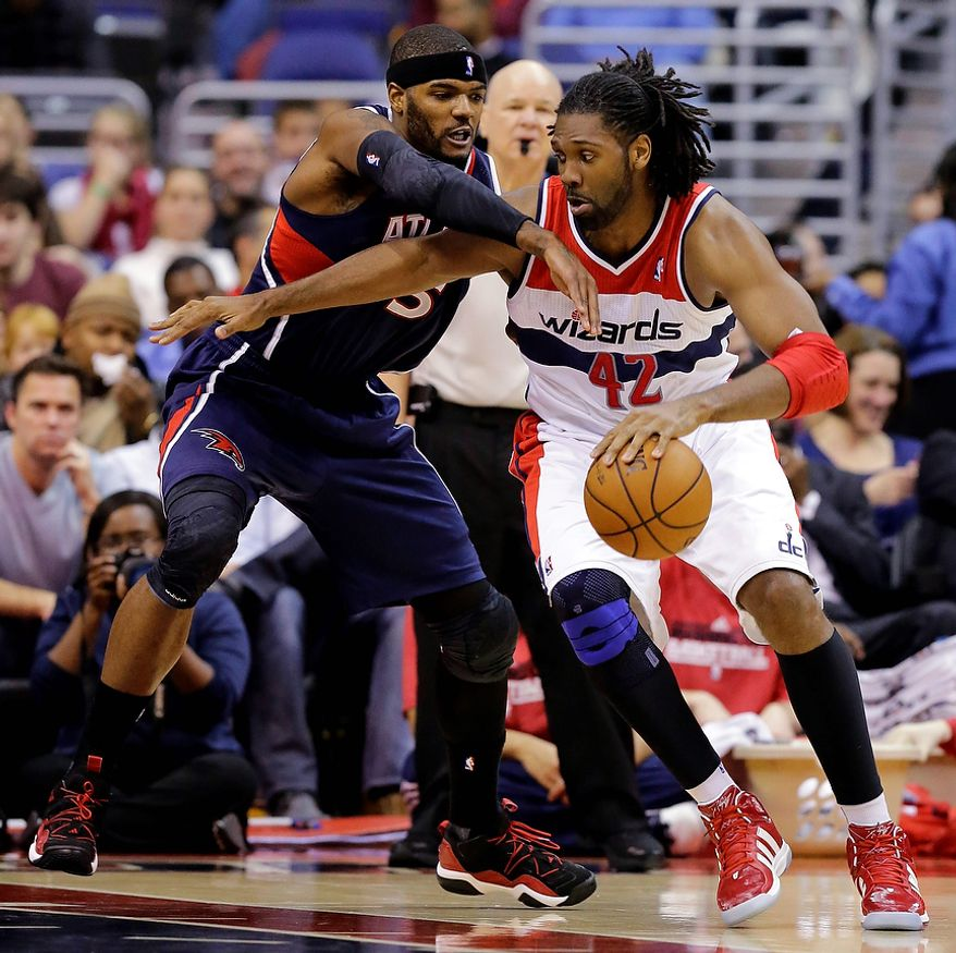 Washington Wizards center Nene, from Brazil, drives with ball against Atlanta Hawks forward Josh Smith in the first half of an NBA basketball game Tuesday, Dec. 18, 2012, in Washington. (AP Photo/Alex Brandon)
