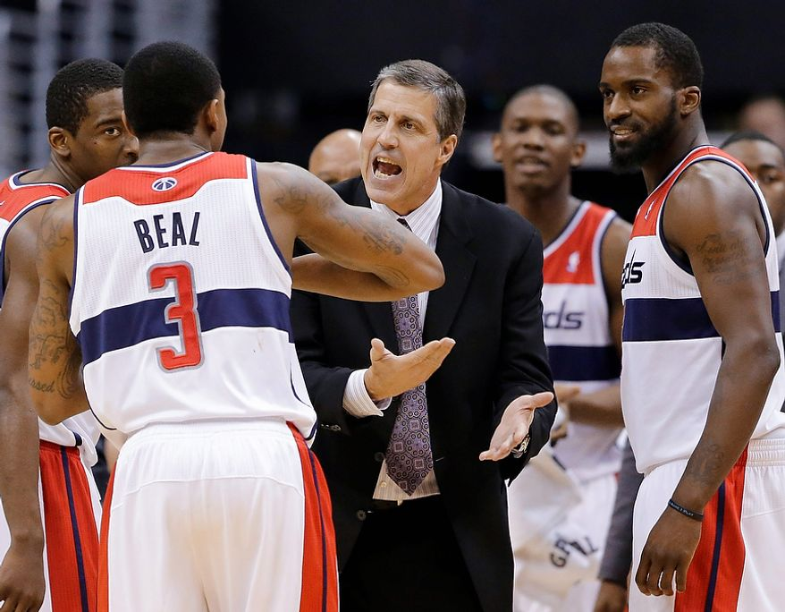Washington Wizards coach Randy Wittman talks with Jordan Crawford, left, Bradley Beal, and Martell Webster, right, during a timeout in the second half of an NBA basketball game against the Atlanta Hawks on Tuesday, Dec. 18, 2012, in Washington. The Hawks won 100-95 in overtime. (AP Photo/Alex Brandon)