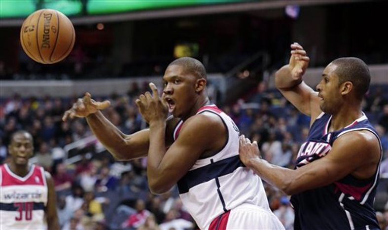 Washington Wizards forward Kevin Seraphin passes the ball in front ot Atlanta Hawks center Al Horford during the second half of an NBA game Tuesday, Dec. 18, 2012, in Washington. The Hawks won 100-95 in overtime. (AP Photo/Alex Brandon)