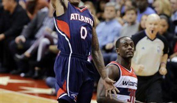 Atlanta Hawks guard Jeff Teague goes up for a duynk as Washington Wizards center Earl Barron watches, during the second half of an NBA basketball game Tuesday, Dec. 18, 2012, in Washington. Teague scored 13 points, as the Hawks won 100-95 in overtime. (AP Photo/Alex Brandon)
