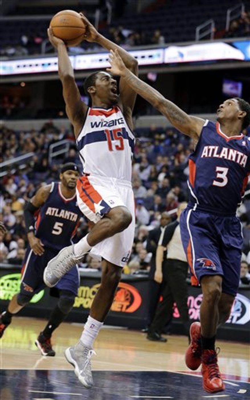Washington Wizards guard Jordan Crawford shoots over Atlanta Hawks guard Louis Williams during overtime of an NBA basketball game Tuesday, Dec. 18, 2012, in Washington. Crawford had 27 points, but the Hawks won 100-95 in overtime. (AP Photo/Alex Brandon)