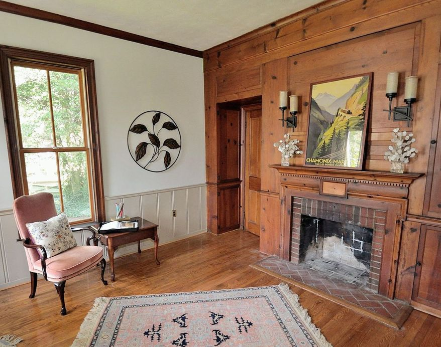 The library has original wood paneling and the original fireplace.