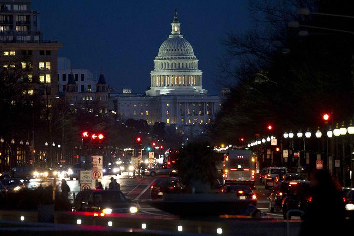 ** FILE ** Red lights illuminate Pennsylvania Avenue as the U.S. Capitol glows in the twilight, in Washington, Wednesday, Dec. 19, 2012. (AP Photo/Jacquelyn Martin)