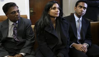 Annie Dookhan (center) sits between two unidentified men in Suffolk Superior Court in Boston moments before her arraignment on Thursday, Dec. 20, 2012. Ms. Dookhan, the former chemist at the center of a drug-testing scandal, pleaded not guilty to charges including perjury and tampering with evidence. (AP Photo/Steven Senne, Pool)